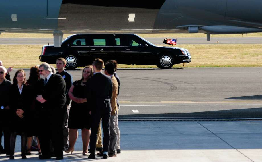 A Presidential limo is seen driving past Air Force One as people gathered on the runway look on at King County International Airport on Tuesday, July 24, 2012. Obama is in town for the third time this year to raise money at two private fundraising events and will stay overnight in Bellevue before departing Wednesday morning. The two events, one at former Costco CEO Jim Sinegal's house, the other a larger reception of about 200, are expected to contribute around $1.75 million towards Obama's re-election campaign. Photo: LINDSEY WASSON / SEATTLEPI.COM
