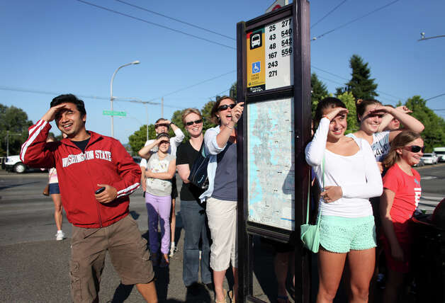 Pedestrians and bus riders wait behind a sign on the Montlake overpass as the motorcade of U.S. President Barack Obama passes near the University of Washington on State Route 520. The President was in Seattle for a visit to raise money for his campaign. For about 15 minutes before the motorcade passed the bridge was shut to pedestrians and people were told by police to wait behind the sign.. Photo: JOSHUA TRUJILLO / SEATTLEPI.COM