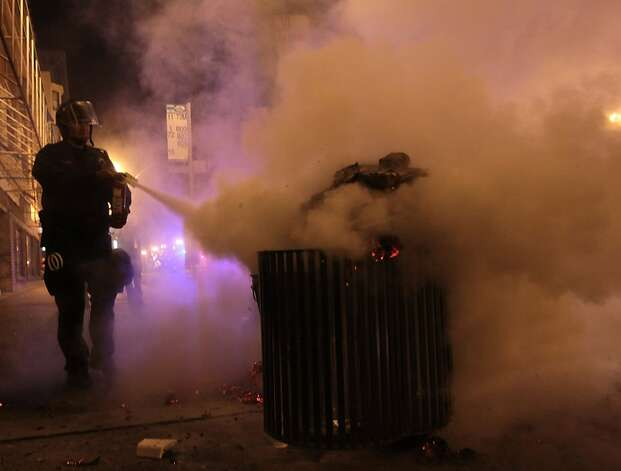 A police officer puts our a fire during an Occupy protest in Oakland, Calif. on Tuesday, May 1, 2012. Photo: Mathew Sumner, Special To The Chronicle