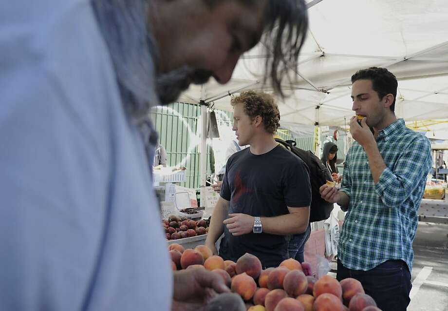 Rob Spiro, right, and Alon Salant, center, co-founders of Good Eggs Inc., try out peaches at stand of Twin Girls Farms at Mission Community Market on Thursday, July 19, 2012 in San Francisco, Calif. Twin Girls Farms uses Good Eggs's software to sell their products. Photo: Yue Wu, The Chronicle