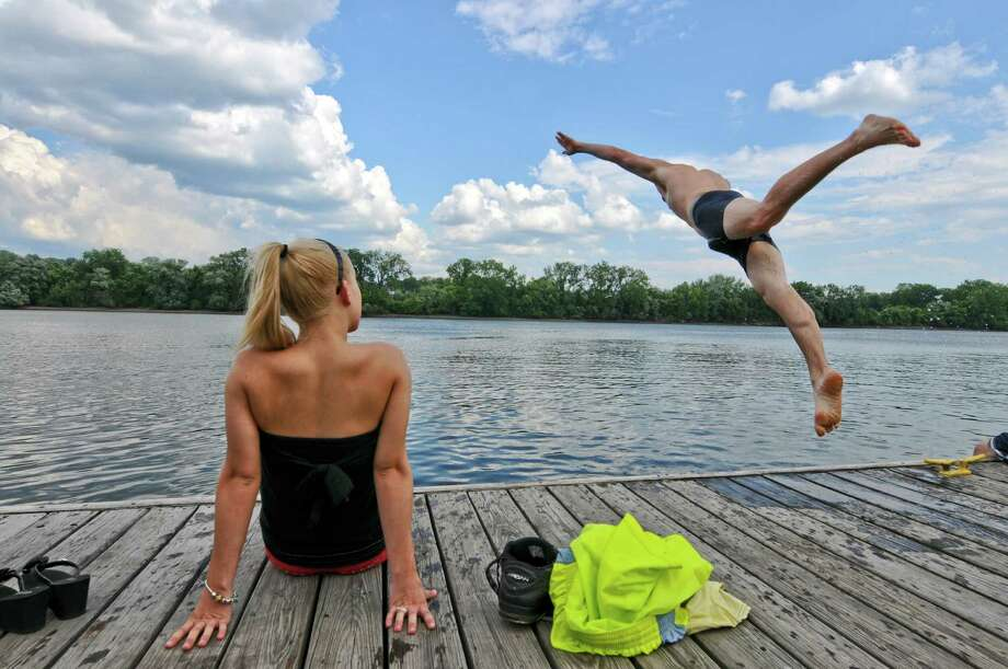 "Mike Smith of Wynantskill jumps into the Hudson River while his girlfriend Kellie St. Pierre of North Greenbush watches, while on his day off as manager of Mantello's, a pizzeria in nearby Rensselaer, on Tuesday July 24, 2012 in Albany, NY.  Kellie's brother Jim was also with them. ""It's perfect,"" said Mike of the water.   (Philip Kamrass / Times Union) Photo: Philip Kamrass"