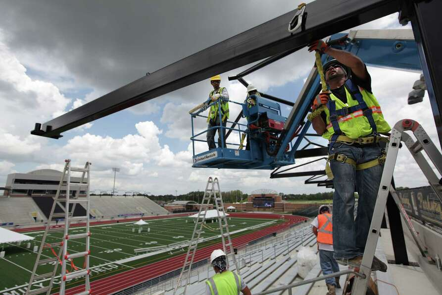 Eric Garcia and fellow workers set up the awning along the bleachers in preparation for the AAU Juni