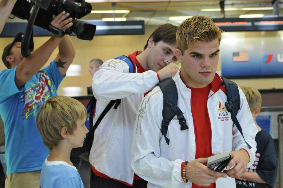 U.S. Olympic judo team member Kyle Vashkulat signs an autograph for Tobias Green of Cooperstown, 9, left, on the shoulder of fellow team member Nick Delpopolo at Albany International Airport before catching a flight to London where they will compete in the Olympics, on Tuesday July 24, 2012 in Colonie, NY.  Both are students at the Jason Morris Judo Center in Glenville. Green was in the airport to see his cousin Ben Blunt, 9, far right, head back home to London, after visiting Tobias family here.  (Philip Kamrass / Times Union) Photo: Philip Kamrass / 00018579A