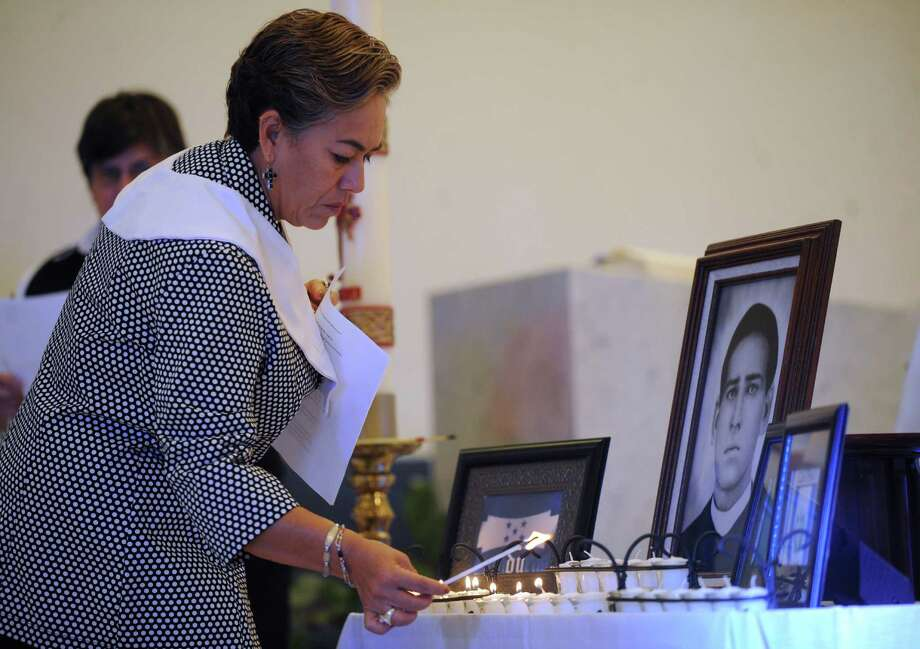 Socorro Davila attends a Mass on Tuesday in Victoria for those who      died in the crash. An image of St. Toribio Romo Gonzalez, patron saint of      immigrants, and the flags of Honduras, Guatemala and Mexico are present. Photo: Billy Calzada / © 2012 San Antonio Express-News