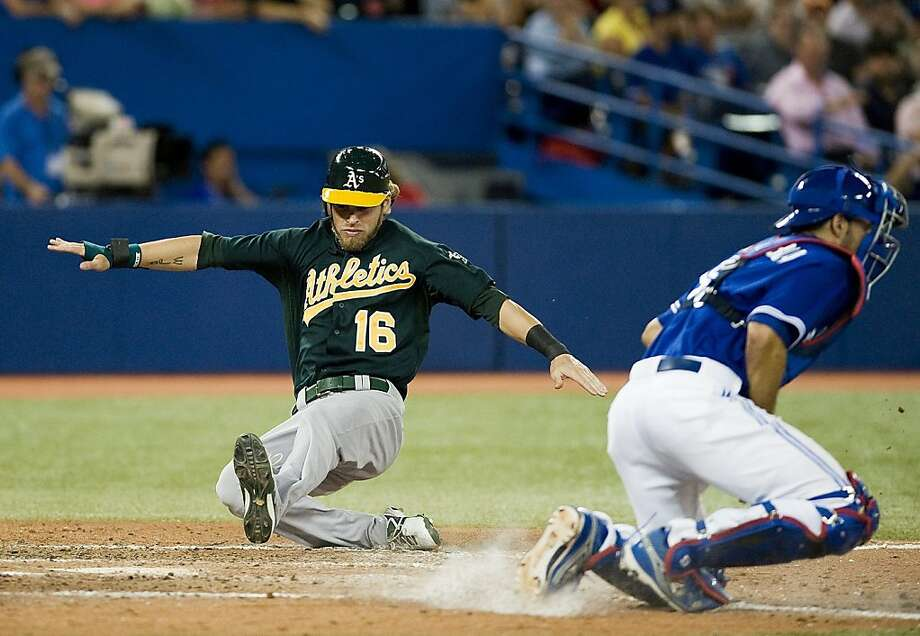 Oakland Athletics' Josh Reddick slides into home on a three-run single hit by Yoenis Cespedes against the Toronto Blue Jays during the seventh inning of a baseball game,Tuesday, July 24, 2012, in Toronto. The Athletics won 7-2. (AP Photo/The Canadian Press, Aaron Vincent Elkaim) Photo: Aaron Vincent Elkaim, Associated Press