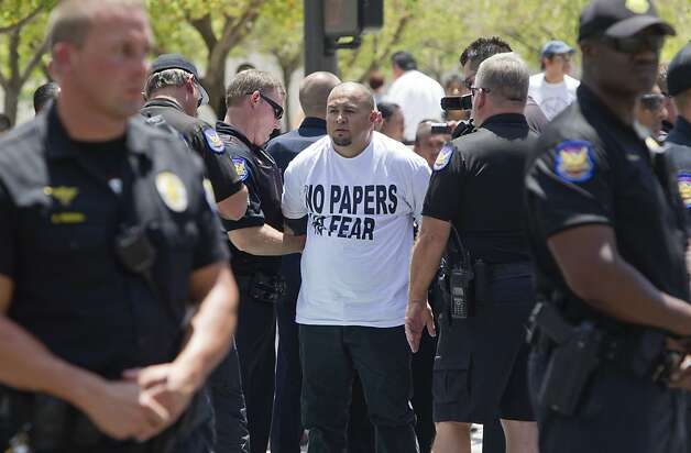 Miguel Guerra of Phoenix gets arrested by Phoenix Police on Fourth Avenue and Washington Street in front of U.S. District Courthouse in Phoenix on Tuesday, July 24, 2012. Guerra was arrested after sitting down and blocking the intersection for an hour in protest of Maricopa County Sheriff Joe Arpaio. (AP Photo/The Republic, Nick Oza) Photo: Nick Oza, Associated Press