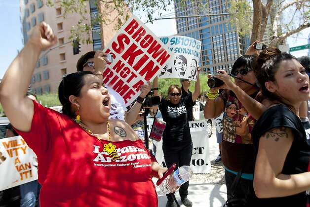 Jovana Renteria, of Phoenix, left, protests against Maricopa County Sheriff Joe Arpaio in front of the U.S. District Courthouse in Phoenix on Tuesday, July 24, 2012. Arpaio was on the witness stand today for a federal racial profiling lawsuit involving his office. (AP Photo/The Arizona Republic, David Wallace)  MARICOPA COUNTY OUT; MAGS OUT; NO SALES Photo: David Wallace, Associated Press