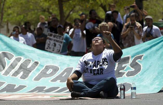 Leticia Ramirez, center, of Phoenix blocks the intersection in protest against Maricopa County Sheriff Joe Arpaio, before getting arrested by Phoenix Police on Fourth Avenue and Washington Street in front of U.S. District Courthouse in Phoenix, Tuesday, July 24, 2012. (AP Photo/The Republic, Nick Oza) Photo: Nick Oza, Associated Press