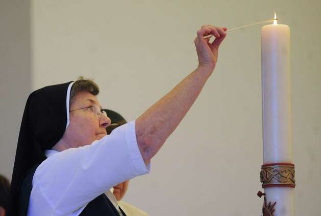 Sister Stephana Marbach prepares to light a candle during a Mass said at Capilla de la Santa Trinidad in Victoria on Tuesday, July 24, 2012, for the 15 immigrants that died as a result of a horrific wreck in Goliad County on Sunday. Photo: Billy Calzada, San Antonio Express-News / © 2012 San Antonio Express-News