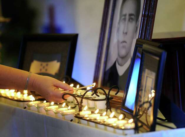 Candles are lit by the flags of Honduras, Guatemala and Mexico and an image of St. Toribio Romo Gonzalez during a Mass on Tuesday, July 24, 2012, in honor of 15 immigrants that died in a wreck in Goliad on Sunday. Photo: Billy Calzada, San Antonio Express-News / © 2012 San Antonio Express-News
