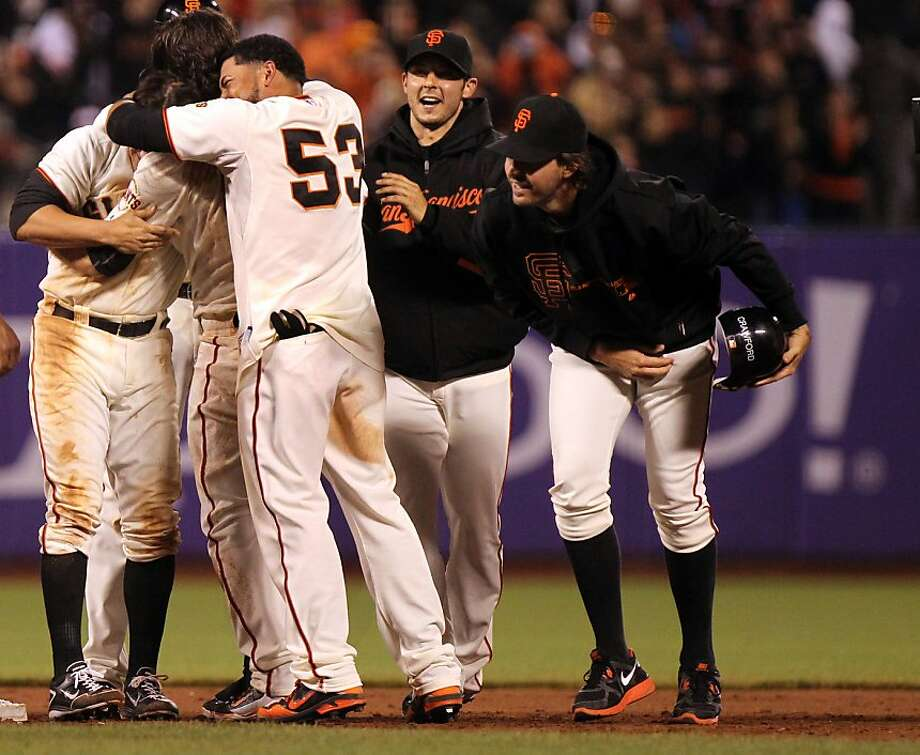 San Francisco Giants Melky Cabrera, and Ryan Theriot hug Brandon Crawford in celebration after he hitthe game winning RBI that scored Brandon Belt in the 9th inning giving the Giants a 3-2 win over the San Diego Tuesday, July 24, 2012 in San Francisco Calif., Photo: Lance Iversen, The Chronicle