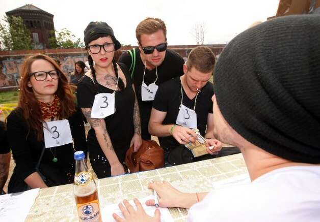 BERLIN, GERMANY - JULY 21:  Attendees sign up to compete at the second annual Hipster Olympics on July 21, 2012 in Berlin, Germany.  (Adam Berry / Getty Images)