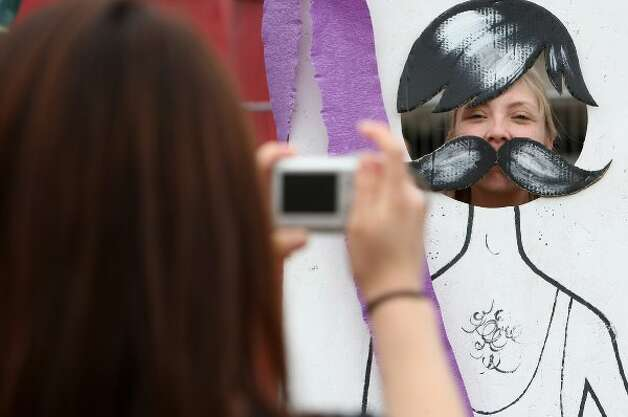 BERLIN, GERMANY - JULY 21:  An attendee photographs another as an ironic-moustache-wearing hipster at the second annual Hipster Olympics on July 21, 2012 in Berlin, Germany.  (Adam Berry / Getty Images)