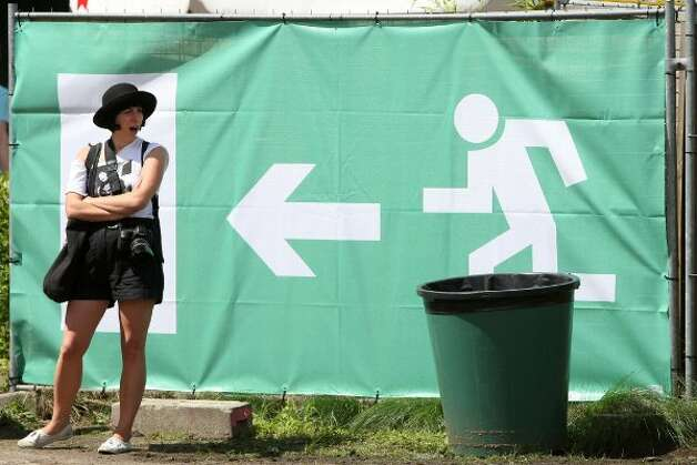 BERLIN, GERMANY - JULY 21:  An attendee yawns by an exit sign at the second annual Hipster Olympics on July 21, 2012 in Berlin, Germany.  (Adam Berry / Getty Images)