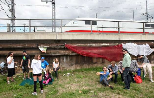 BERLIN, GERMANY - JULY 21:  Attendees wait for the start of the games as a Deutsche Bahn ICE (InterCity Express) train passes overhead at the second annual Hipster Olympics on July 21, 2012 in Berlin, Germany.  (Adam Berry / Getty Images)