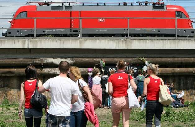BERLIN, GERMANY - JULY 21:  Attendees wait for the start of the games as a Deutsche Bahn regional train passes overhead at the second annual Hipster Olympics on July 21, 2012 in Berlin, Germany. (Adam Berry / Getty Images)