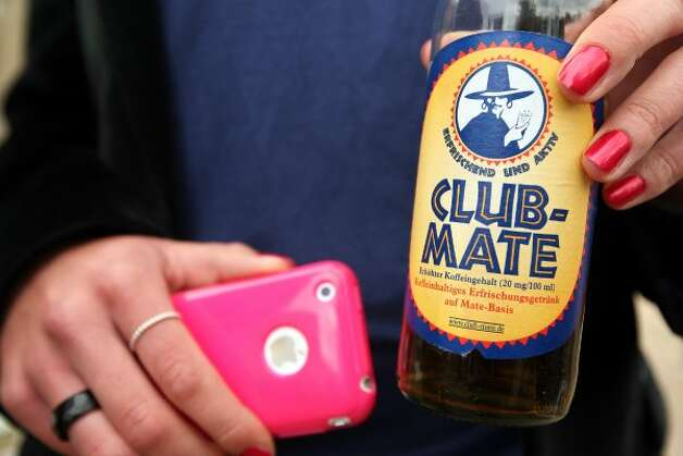 BERLIN, GERMANY - JULY 21:  A visitor shows her bottle of Club-Mate carbonated yerba mate drink during the second annual Hipster Olympics on July 21, 2012 in Berlin, Germany.  (Adam Berry / Getty Images)