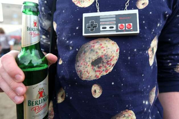 BERLIN, GERMANY - JULY 21:  An attendee wearing a 1980s Nintendo controller as a necklace holds a Berliner Pilsener beer at the second annual Hipster Olympics on July 21, 2012 in Berlin, Germany. (Adam Berry / Getty Images)