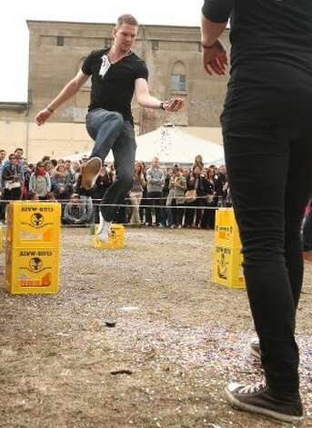 "BERLIN, GERMANY - JULY 21:  Contestants compete in the ""Confetti Toss"" event, in which competitors must jump over sticks laid across empty Club-Mate crates and pass confetti to one another, at the second annual Hipster Olympics on July 21, 2012 in Berlin, Germany.  (Adam Berry / Getty Images)"
