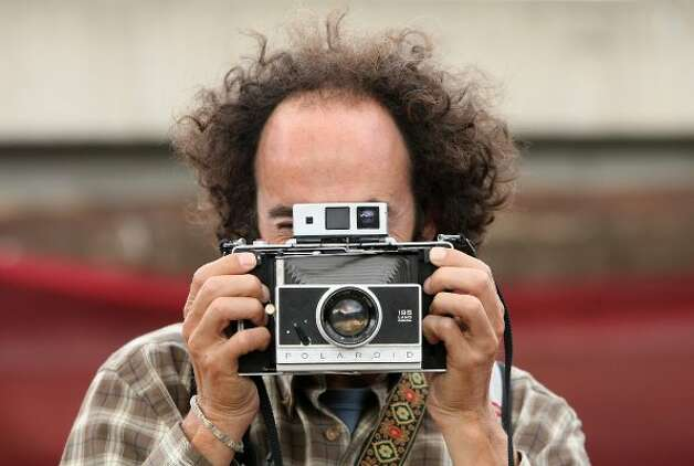 BERLIN, GERMANY - JULY 21:  An attendee tries out a Polaroid Land Camera at the second annual Hipster Olympics on July 21, 2012 in Berlin, Germany. (Adam Berry / Getty Images)