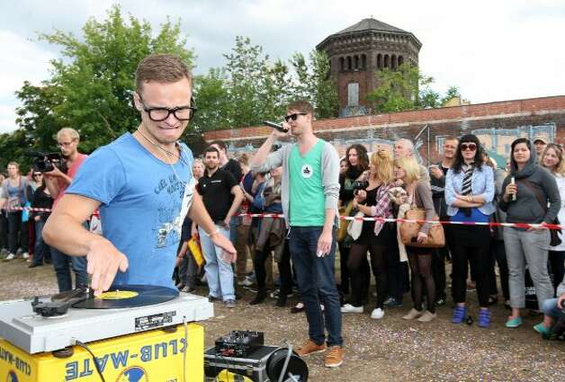 "BERLIN, GERMANY - JULY 21:  A contestant competes in the ""Vinyl Record Spinning Contest,"" in which competitors must run around a record player while keeping a finger on a record, at the second annual Hipster Olympics on July 21, 2012 in Berlin, Germany. (Adam Berry / Getty Images)"