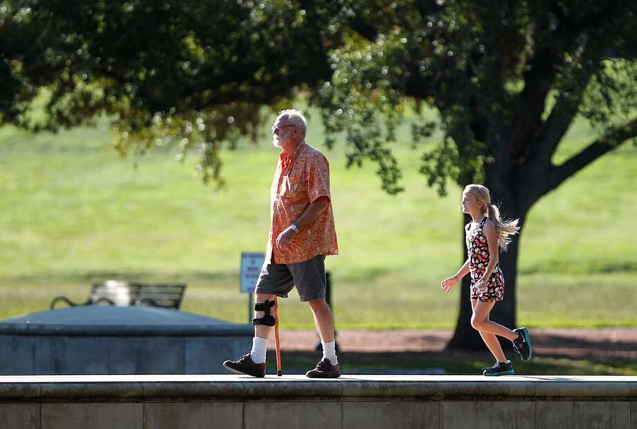 Jerry Harper, left, walks along the wall of Hermann Park's reflecting pool with his granddaughter Emma Harper, 9, on Wednesday, July 25, 2012. Jerry says he has spent many a morning at the park with his granddaughter. Photo: Nick De La Torre