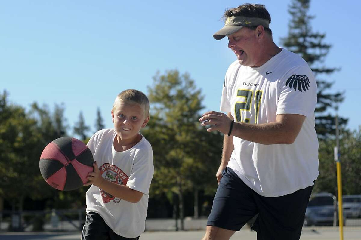 Ken Flax, Olympic hammer-thrower, plays basketball with his son Austin, 9, in Los Altos, Calif., July 20, 2012. Flax competed in the 1988 and 1992 Olympic Games.