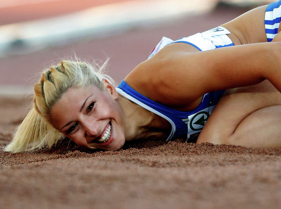 """FILE- Greece's Voula Papachristou lands in the sand after her jump at the Women's Triple Jump final at the European Athletics Championships in Helsinki, Finland, in this file photo dated Friday, June 29, 2012. The Hellenic Olympic Committee has removed triple jumper Voula Papachristou from the team taking part in the upcoming London Olympic Games over comments she made on twitter making fun of African immigrants and expressing support for a far-right party. """"The track and field athlete Paraskevi (Voula) Papachristou is placed outside the Olympic Team for statements contrary to the values and ideas of the Olympic movement,"""" a statement by the Hellenic Olympic Committee says. Papachristou is in Athens, and was to travel to London """"shortly before the track events start,"""" the announcement says.(AP Photo/Matt Dunham, file) Photo: Matt Dunham, STF"""