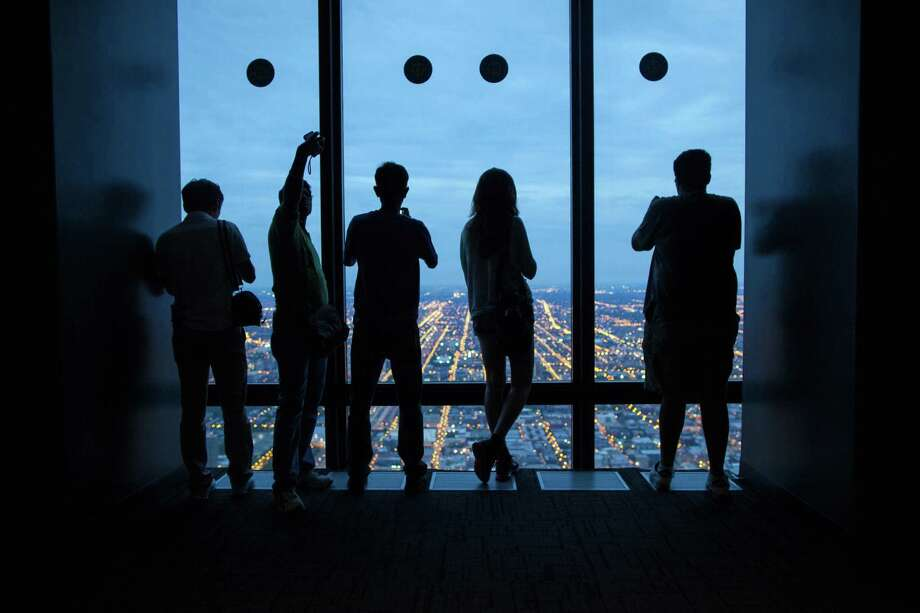 In this June 23, 2012 photo, tourists are silhouetted as they look out the observation deck of the Willis Tower in Chicago. (AP Photo/Sitthixay Ditthavong) Photo: Sitthixay Ditthavong / AP