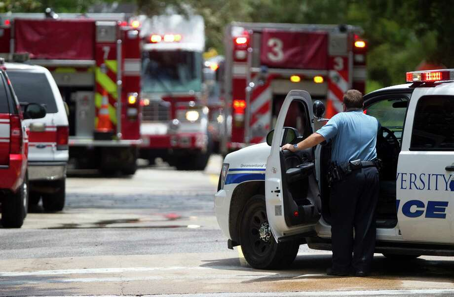A Rice University Police Officer waits outside Dell Butcher Hall as crews work the site of an ammonia leak at Rice University Wednesday, July 25, 2012, in Houston. No injuries were reported. (Cody Duty / Houston Chronicle) Photo: Cody Duty / © 2011 Houston Chronicle