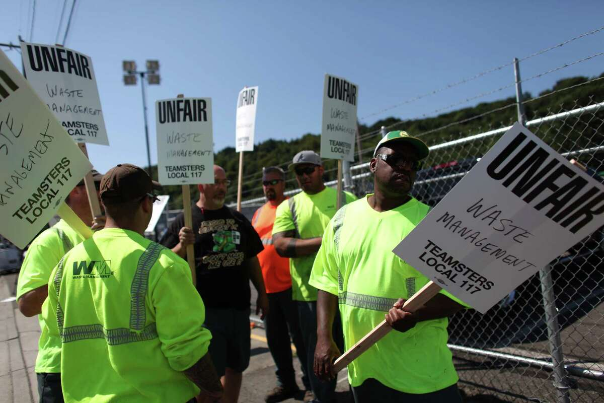 Union members take signs as members of Teamsters Local 117 begin a strike against Waste Management on Wednesday, July 25, 2012. Drivers that pick up yard waste and recycling are striking and some members of Local 174, the trash haulers union, are expected to honor the picket lines.