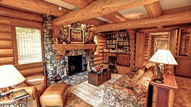 Family room, with river rock fireplace, log crossbeams, mini bar and built-in bookshelves, of a Snoqualmie home set for sale at auction on Aug. 9. Photo: J. P. King Auction Co.