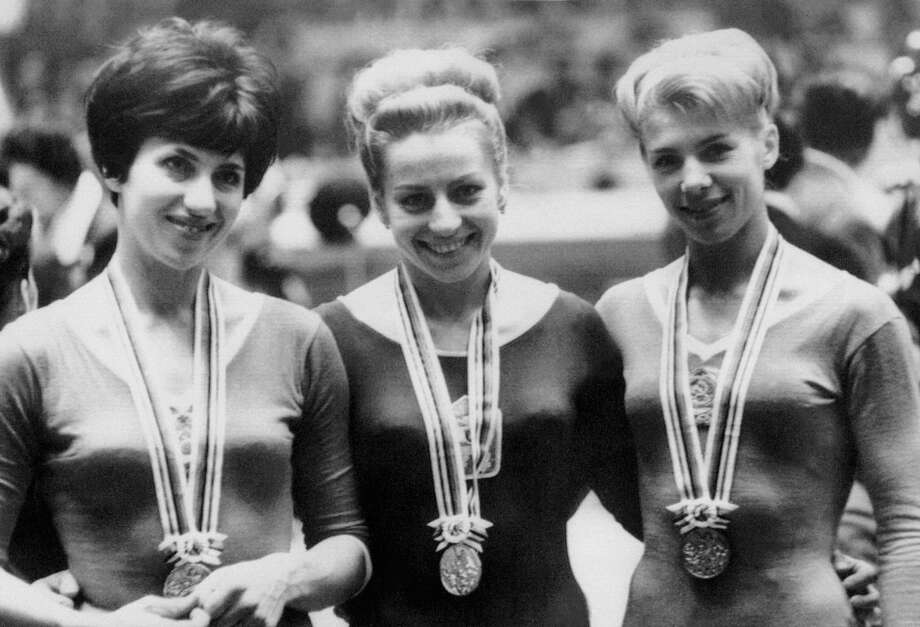 Czech gymnast Vera Caslavska (center), shown here at the 1964 at the Olympic Games in Tokyo, had a moment of political protest during the 1968 Olympics in Mexico City when she tied for gold in the floor exercise. In a display of disregard for Soviet invasion, she turned her head down 