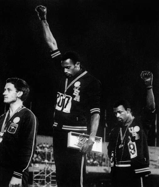 USA athletes Tommie Smith (center) and John Carlos (right) raised their gloved fists in the Black Po