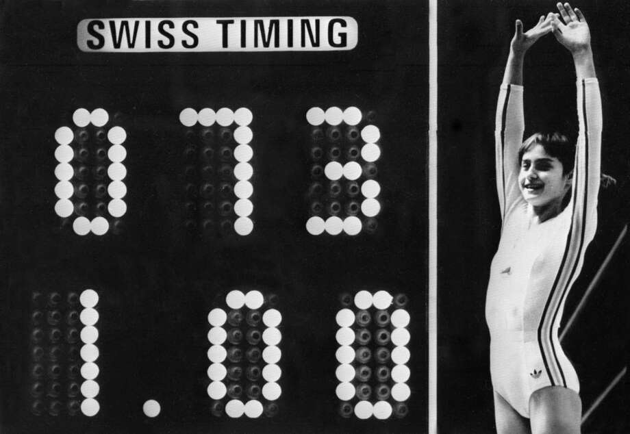 This photo shows Romanian Olympic gymnastics champion Nadia Comaneci celebrating as the scoreboard attempts to show her perfect score of 10 during the 1976 Olympic Games in Montreal. Comeneci was the first to earn the honor after her acrobatic compulsory at uneven bars, and the scoreboard wasn't able to show the number 10. Photo: AFP, Getty Images / 2006 AFP