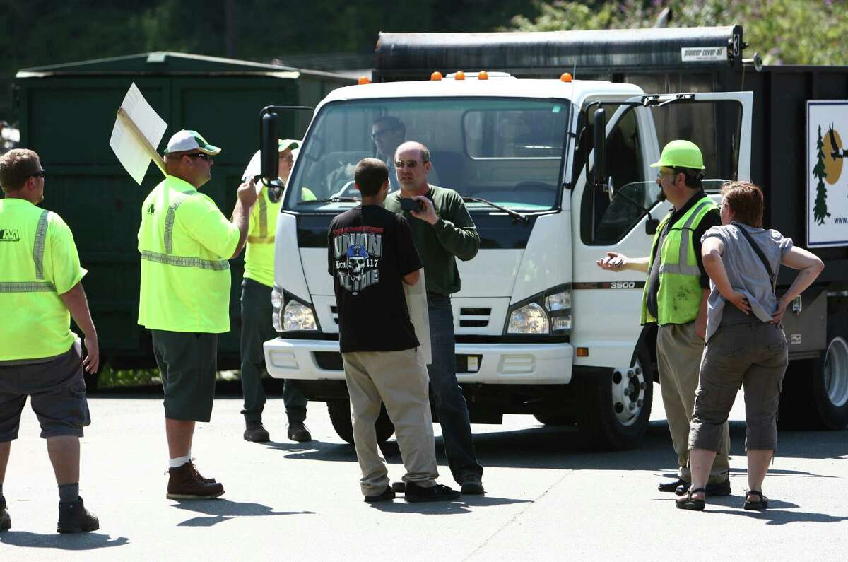A truck driver argues with union members at the Waste Management Transfer Station as members of Teamsters Local 117 block some of the trucks unloading at the facility on Wednesday, July 25, 2012. Drivers that pick up yard waste and recycling are striking and some members of Local 174, the trash haulers union, are expected to honor the picket lines.