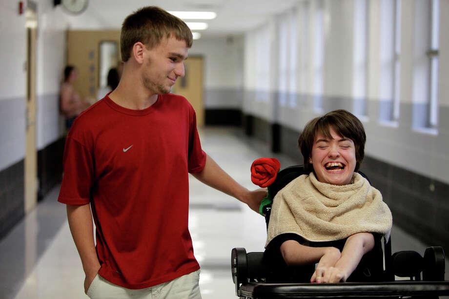Adrian Pressey walks through the halls with Kassie Sanchez and at Clark High School on Thursday, May 10, 2012. Pressey used any free time he had to spend with Kassie, including taking her for walks outside her classroom and making sure she had whatever she needed. Photo: Lisa Krantz, San Antonio Express-News / San Antonio Express-News