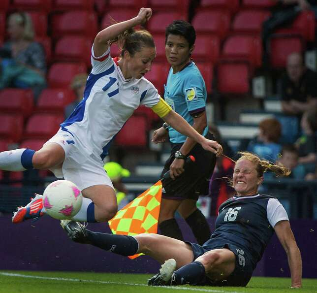 The United States' Rachel Buehler (16) fights for the ball while falling out of bounds with France's