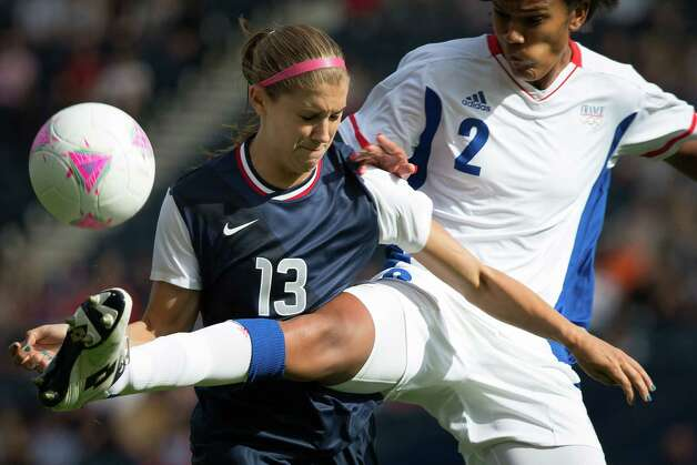 Alex Morgan of the United States, left, fights for a ball against France's Wendie Renard during a women's first round, group G, football match of the 2012 London Olympics on Wednesday, July 25, 2012, at Hampden Park in Glasgow. Photo: Smiley N. Pool, Houston Chronicle / © 2012  Houston Chronicle