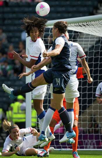 The United States' Abby Wambach (14) knocks a header over France's Wendie Renard for the American's