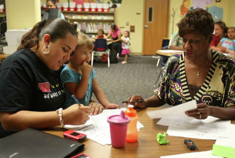 (From left) Michelle Glickman holds her daughter Rihanna, 3, while filling out a Head Start Pre-K application with staff Tina Baker Wednesday July 25, 2012 at Park Village Elementary. If chosen for the program, Glickman would have half a day of Pre-K and the rest of the day at Head Start, making an entire day of school for ages 3-4. Over 100 families are expected to apply for Head Start today. Photo: Julysa Sosa / SAN ANTONIO EXPRESS-NEWS