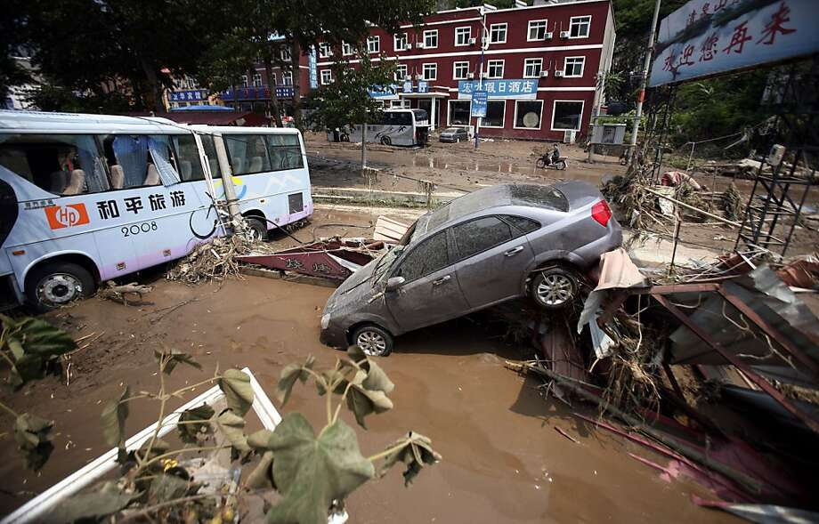 "TOPSHOTS This picture taken on July 24, 2012 shows damaged vehicles after flooding in the town of Laishui in northern China's Hebei province, just north of capital Beijing. Weekend floods in Beijing caused ""significant losses"" and casualty numbers are still being tallied, the head of the worst-hit district has said, as residents of China's capital question the official toll.      CHINA OUT      AFP PHOTOAFP/AFP/GettyImages Photo: Afp, AFP/Getty Images"
