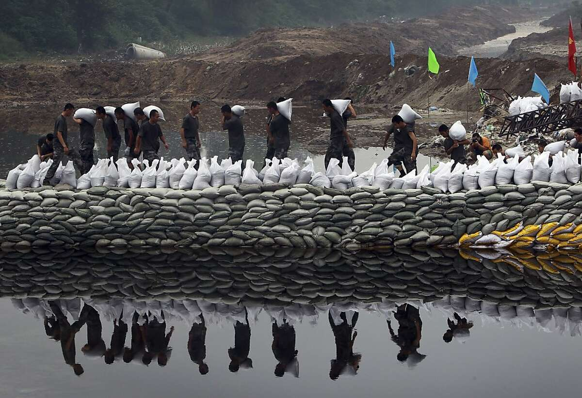 Chinese soldiers carry sandbags to build a makeshift dam to prevent flooding on Dongsha River in Fangshan district in Beijing, China Wednesday, July 25, 2012. Last Saturday's heavy rain was unusual in normally dry Beijing. On Wednesday, July 25 evening, more heavy rain fell on the capital as forecast by the Beijing Meteorological Bureau, which warned of possible flash flooding and mudslides in the capital's mountainous outskirts, including already hard-hit Fangshan. (AP Photo) CHINA OUT