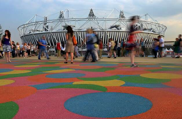 TOPSHOTS Visitors walk past the Olympic Stadium in the Olympic Park before the last rehearsal of the Opening ceremony  in east London on July 25, 2012, two days before the start of the London 2012 Olympic Games. AFP PHOTO / JOHANNES EISELEJOHANNES EISELE/AFP/GettyImages Photo: Johannes Eisele, AFP/Getty Images