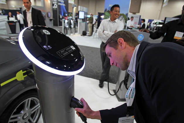 Mike Waters plugs into a GE charger at the Plug-In-2012 Convention & Expo at the Gonzalez Convention Center on July 25, 2012. Photo: Tom Reel / ©2012 San Antono Express-News