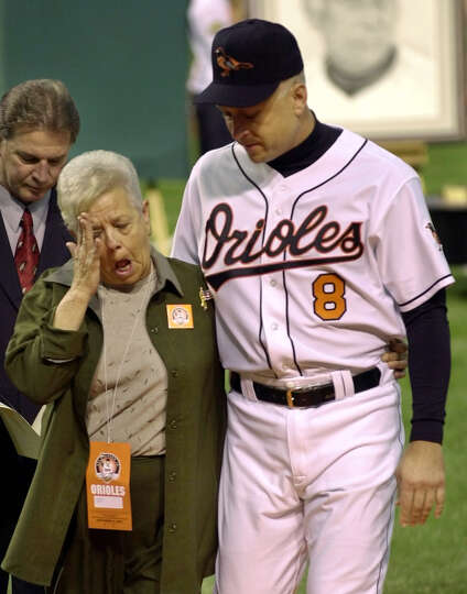 FILE - This Oct. 6, 2001 file photo shows Cal Ripken escorting his mother, Vi, from the field, after