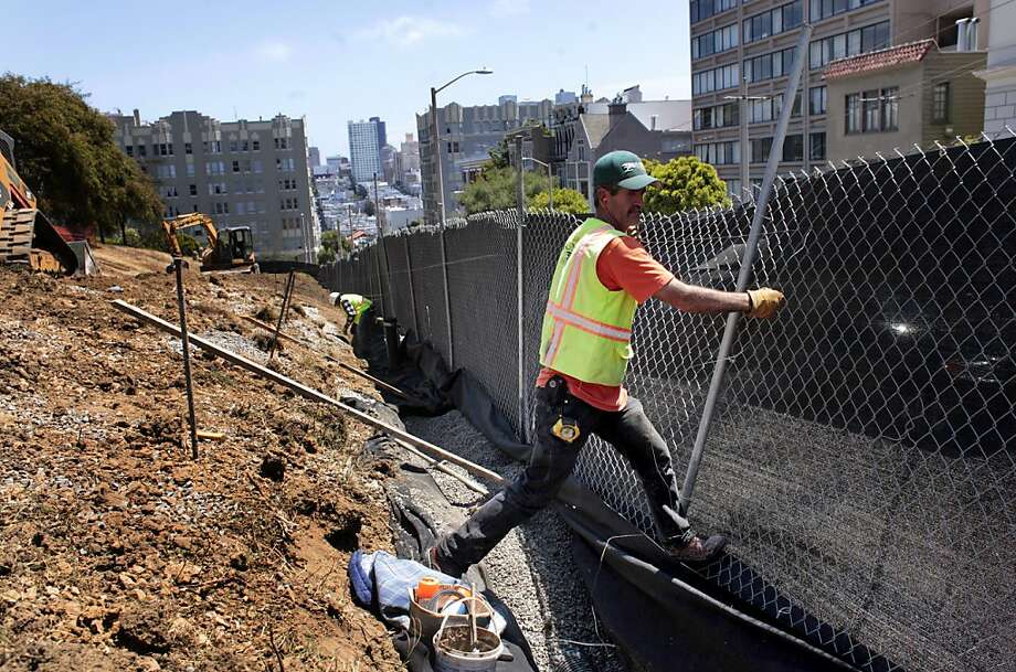 Construction worker Ramiro Romo works at back filling  the fence barrier around Lafayette Park, Wednesday July 25, 2012, in San Francisco, Calif. After a complaint by one resident the renovation has stopped and all but three construction workers have been laid off costing the city close to $10,000 a day. Photo: Lacy Atkins, The Chronicle