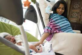 Pooja works from a laptop in her livingroom while her 3 week old son Arjun lays in a near by cradle.  Pooja Sankar started working from home 5 days after giving birth to her son Arjun.   Palo Alto, CA Wednesday July 25th, 2012.