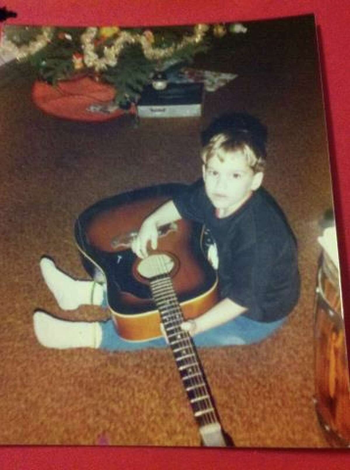 Pat Tiernan, at age 7, sits on the floor with a 12-string guitar. (Courtesy Tiernan family)