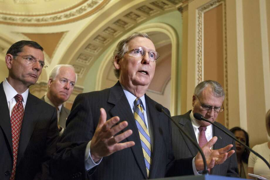 In this July 24, 2012, photo, Senate Minority Leader Mitch McConnell of Ky., gestures during a news conference on Capitol Hill in Washington, following a political strategy session, as from back left, Sen. John Barrasso, R-Wyo., Sen. John Cornyn, R-Texas, and Senate Minority Whip Jon Kyl of Ariz., listen. The Senate is bracing for a tax-cut showdown that is all about Democrats and Republicans showing voters their differences over taxing the well-off while accusing each other of threatening to shove the government over a fiscal cliff. Senators planned to vote Wednesday, July 25 on a $250 billion Democratic bill that would extend expiring tax cuts next year for all but the highest earners. Republicans were forcing Reid to corral 60 votes for the proposal, which he does not have.  (AP Photo/J. Scott Applewhite) Photo: J. Scott Applewhite / AP